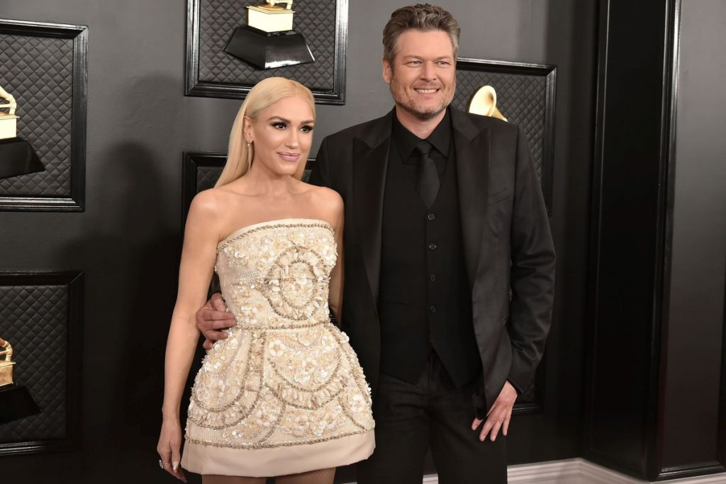 Gwen Stefani is a white dress and Blake Shelton wears a black suit at the Grammy's red carpet