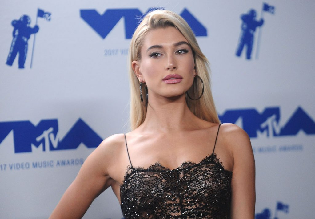 Hailey Bieber standing in front of a blue and white background
