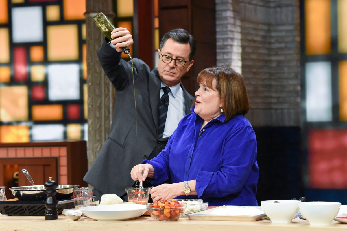 Ina Garten cooks with Stephen Colbert, seen pouring oil