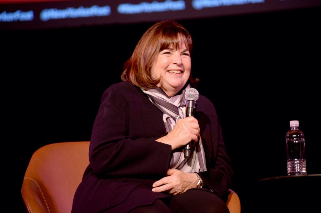 Ina Garten sits onstage as she smiles and speaks into a microphone at an event during the 2019 New Yorker Festival