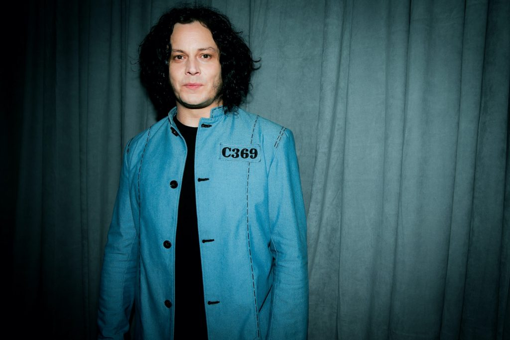 Jack White smiling in front of a green curtain