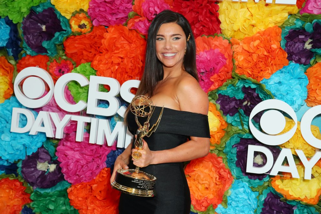 Jacqueline MacInnes Wood smiling in front of a multicolored background