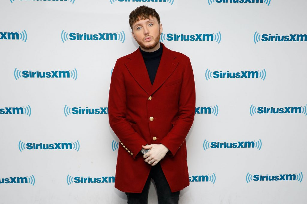 James Arthur smiling in front of a white background