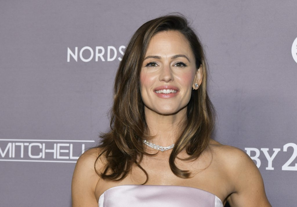 Jennifer Garner smiling in front of a gray background