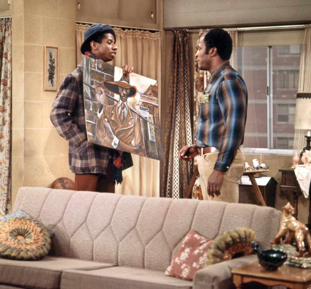 Jimmie Walker holds a painting in front of John Amos