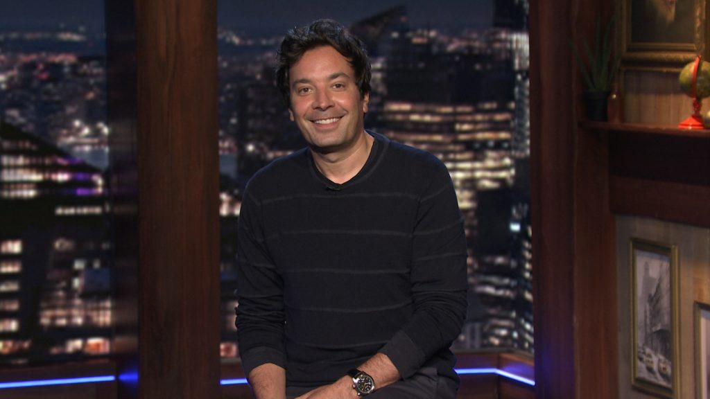 Jimmy Fallon smiling in front of a window
