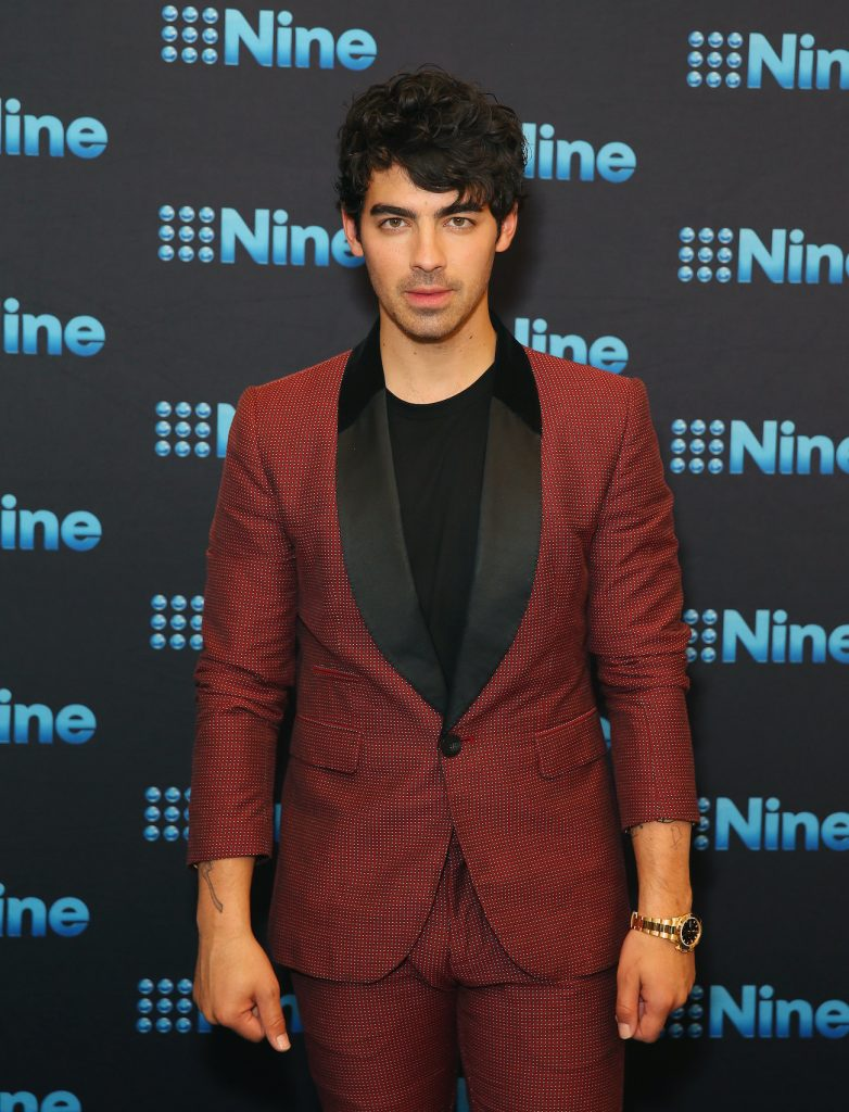 Joe Jonas attends the Nine All Stars Event in a red suit