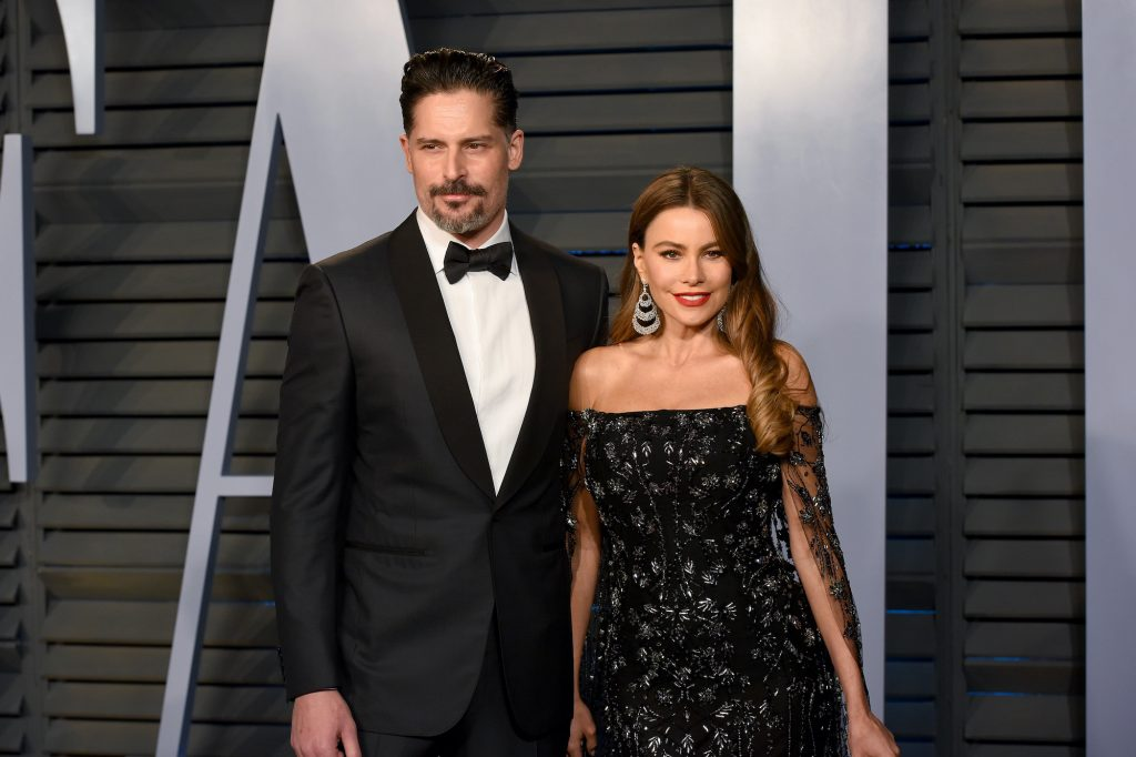 (L-R) Joe Manganiello and Sofia Vergara smiling in front of a gray background