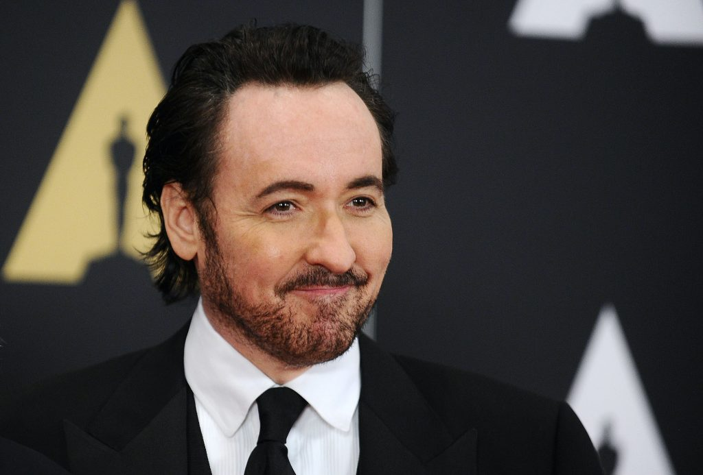 John Cusack smiling in front of a black background