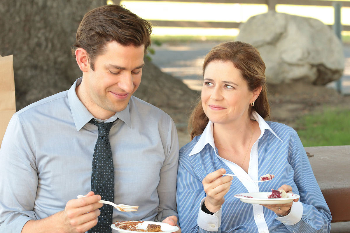 The Office Jenna Fischer and John Krasinski smile while eating pie as Jim and Pam.