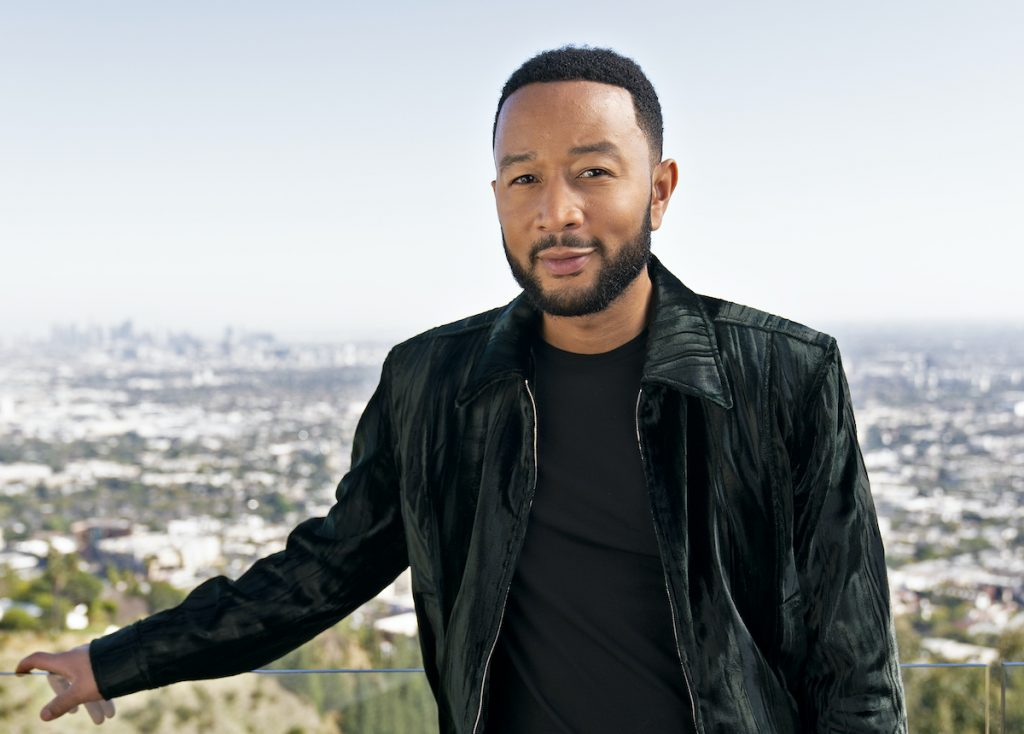 John Legend in a dark green coat standing in front of a city skyline   Troy Harvey/ABC via Getty Images