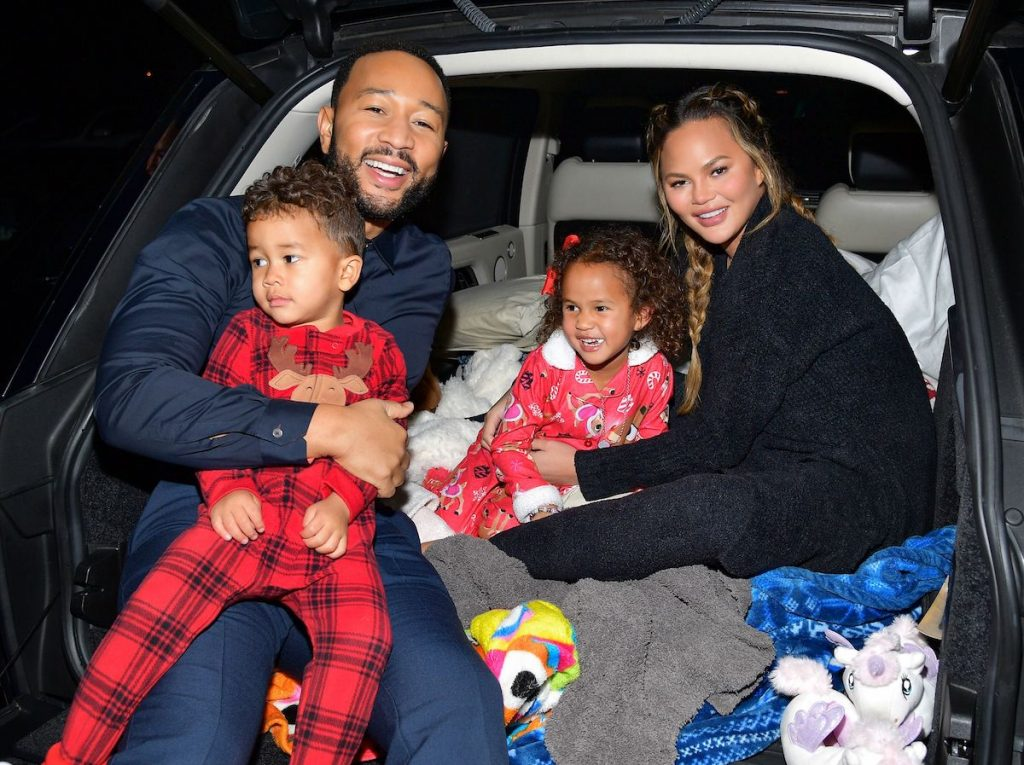 John Legend, Chrissy Teigen, and their children, Luna Stephens and Miles Stephens, sit in the back of a car at Netflix's 'Jingle Jangle: A Christmas Journey' drive-in premiere | Matt Winkelmeyer/Getty Images for Netflix