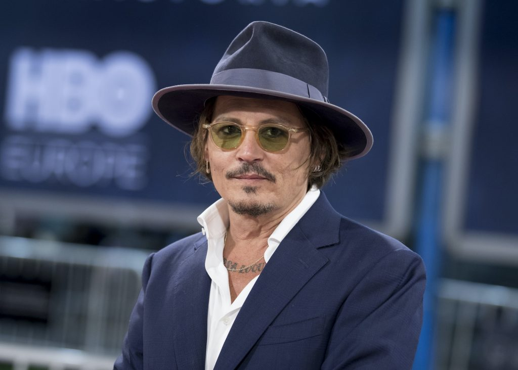 Johnny Depp in a hat and glasses in front of a blurred blue background