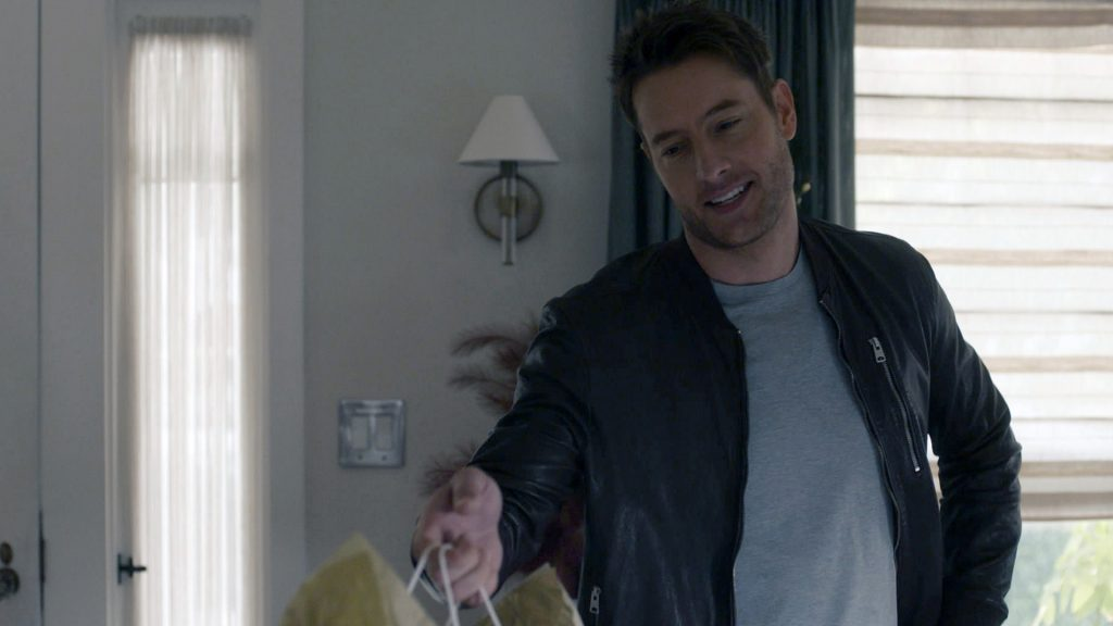 Justin Hartley as Kevin Pearson handing out a gift in 'This Is Us' Season 5 Episode 10