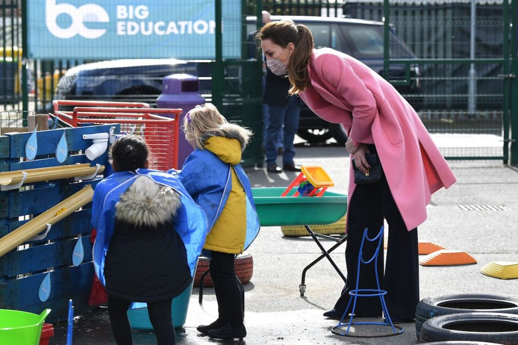 Kate Middleton leaning over and talking to children wearing a pink peacoat and black pants.