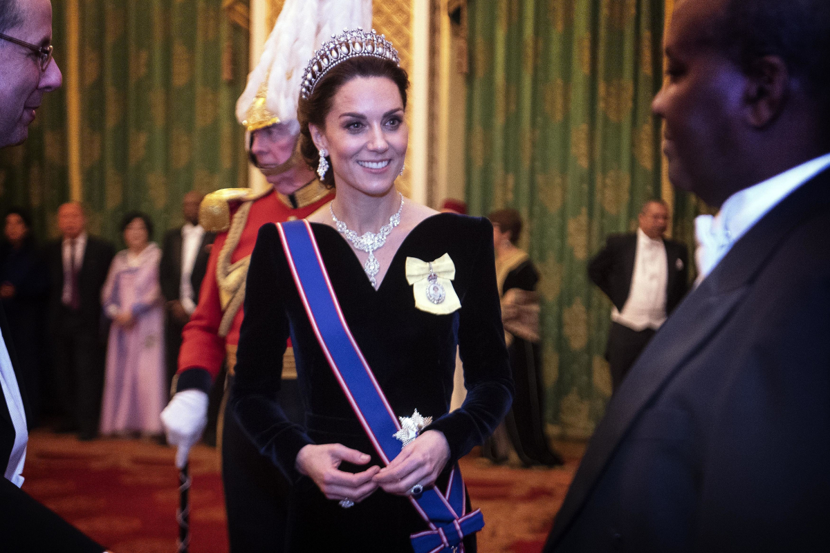 Kate Middleton talks to guests at an evening reception for members of the Diplomatic Corps at Buckingham Palace on December 11, 2019