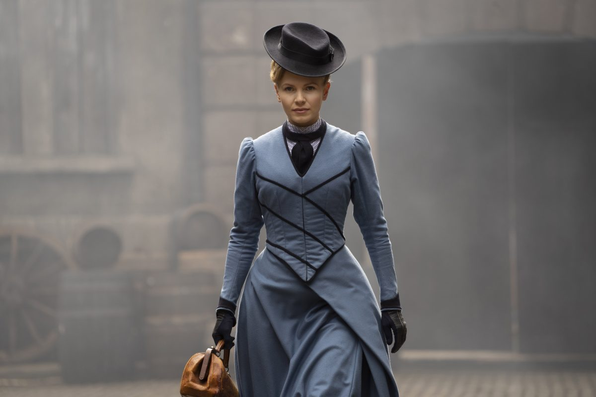 Kate Phillips, in a blue dress, as Eliza Scarlet in Miss Scarlet and the Duke