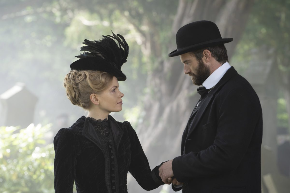 Kate Phillips and Stuart Martin, both dressed in black, looking at each other in an episode of Miss Scarlet and the Duke
