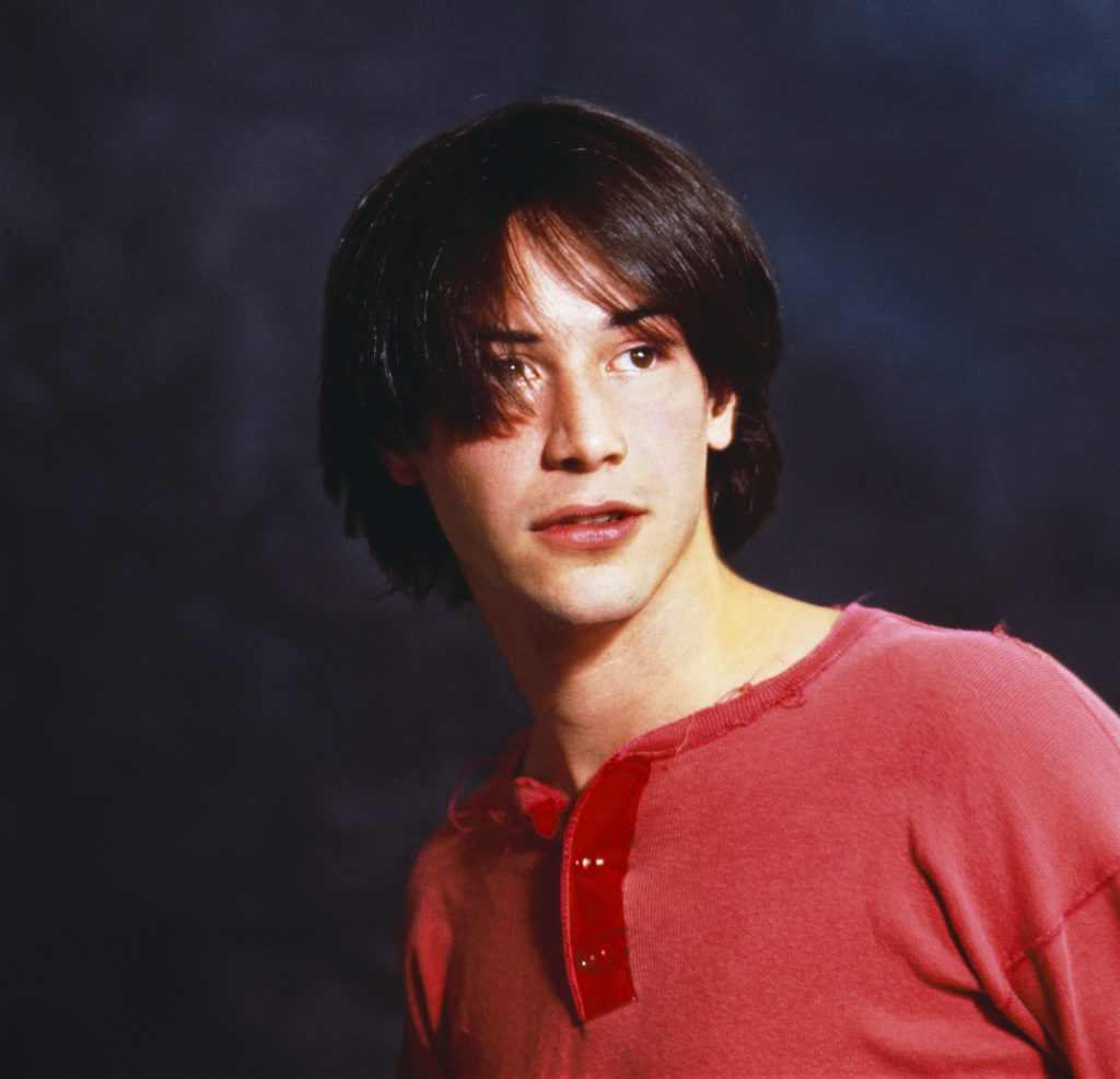 A young Keanu Reeves, with a wispy bowl haircut and a red henley shirt, poses in a photo studio
