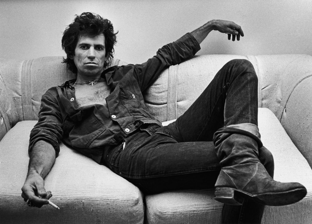 Keith Richards sitting on a couch, holding a cigarette, in black and white