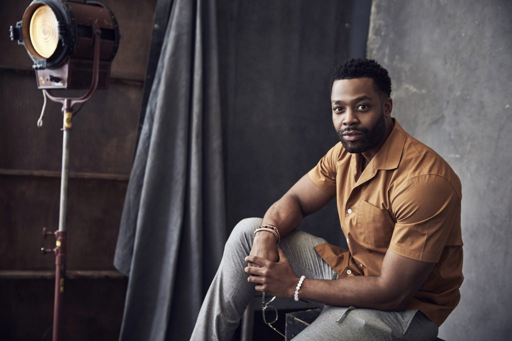 LaRoyce Hawkins smiling, posed on a block in front of a gray background and vintage photography light