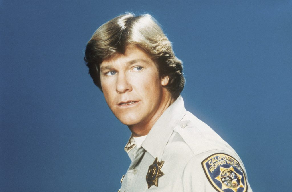 Larry Wilcox as Officer Jon Baker looking off camera in front of a blue background