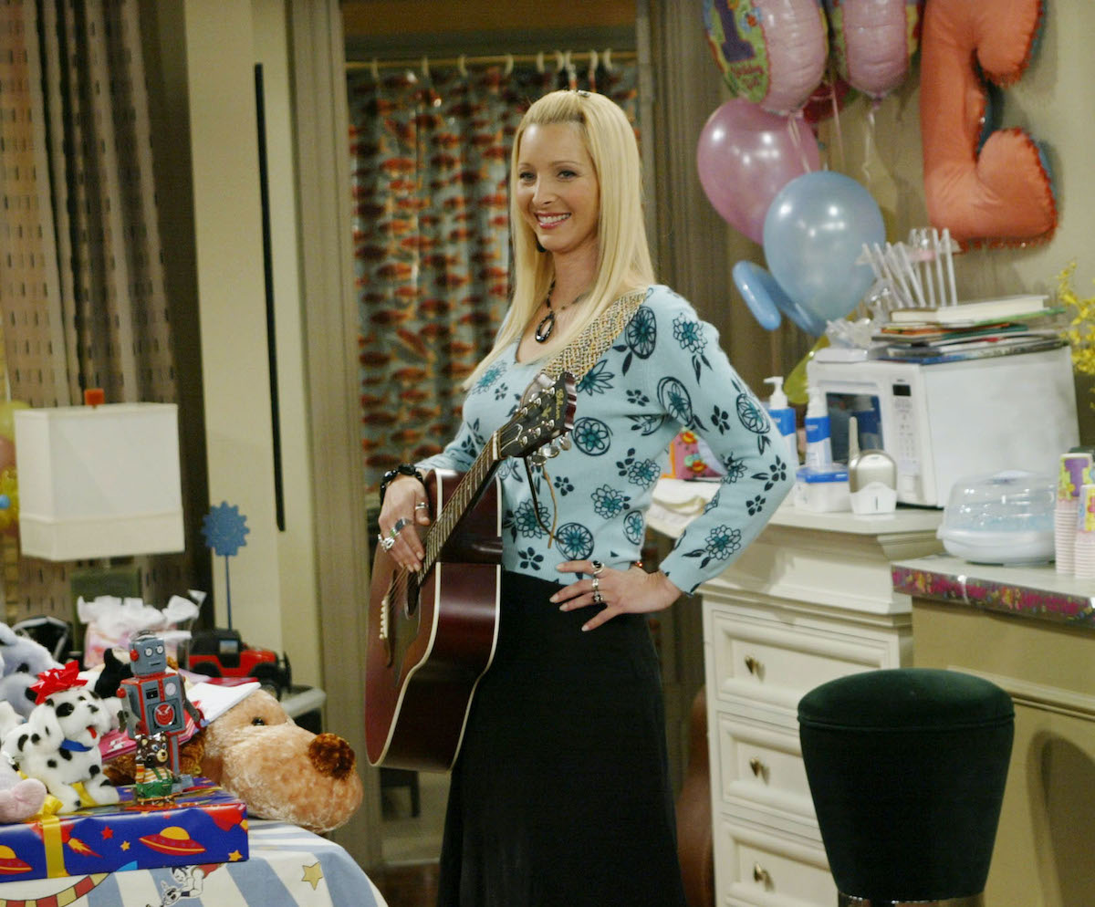 Lisa Kudrow as Phoebe Buffay on 'Friends' stands with a guitar at a party.