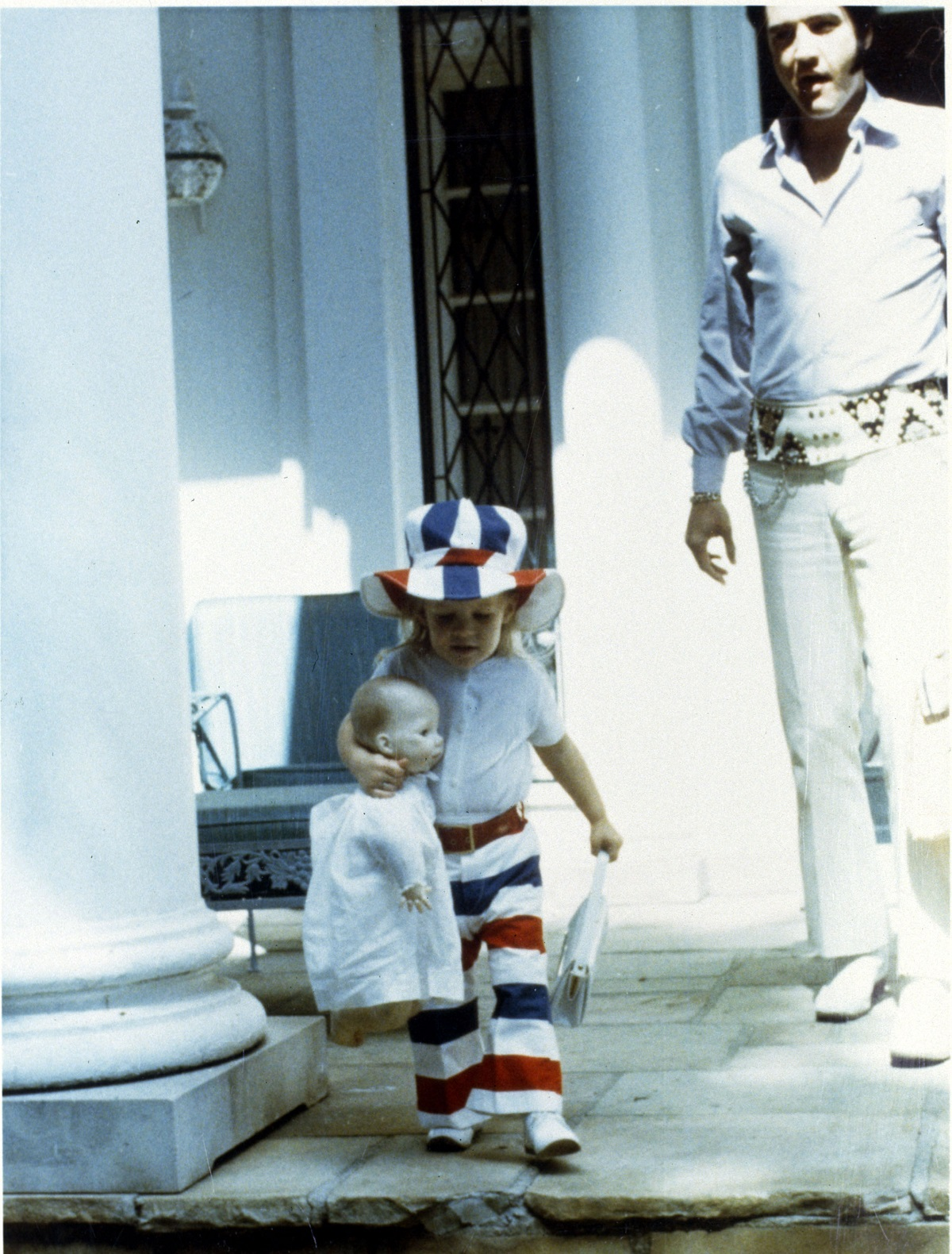Lisa Marie Presley as a child with a doll with Elvis Presley in the background in a candid shot