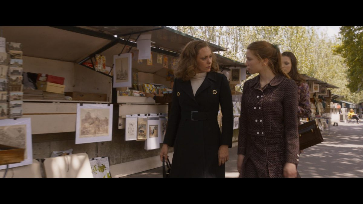 Two women walking by bouquinistes in Paris in Madame Claude