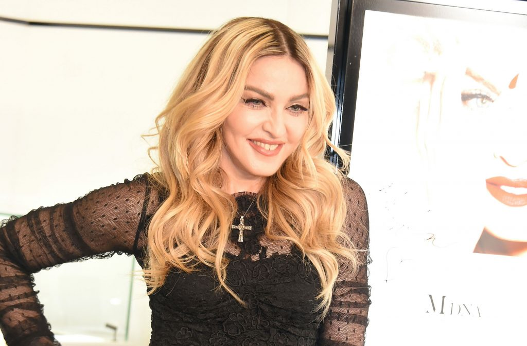 Madonna smiling in front of a white background