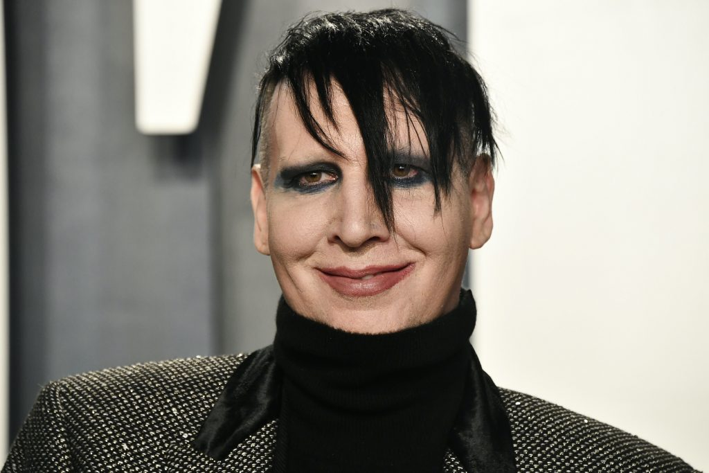 Marilyn Manson smiling in front of a blurred background