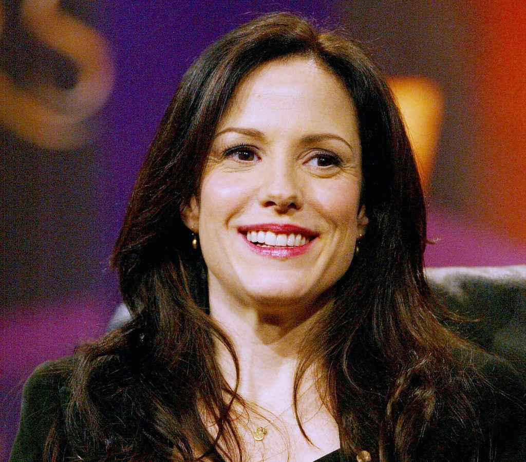 Mary-Louise Parker of 'Weeds' sitting in a chair in front of a purple and orange backdrop | Frederick M. Brown/Getty Images