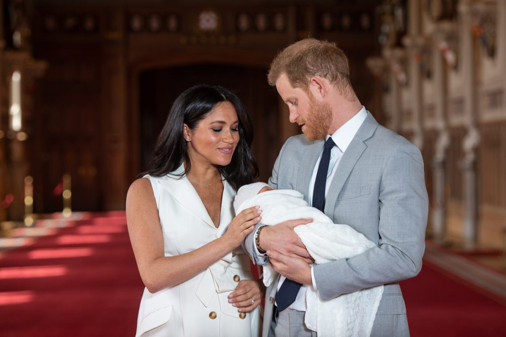 (L-R) Meghan Markle smiling and Prince Harry holding baby Archie