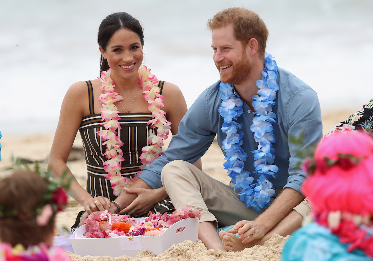 Meghan Markle and Prince Harry sit on the beach in Australia holding hands and smiling