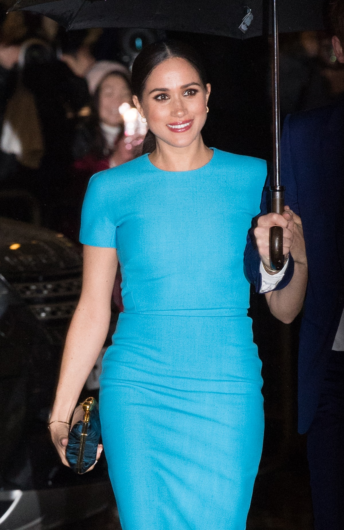 Meghan, Duchess of Sussex, in a blue dress and holding an umbrella and clutch purse on her way to the Endeavour Fund Awards at Mansion House in London in Mar. 2020
