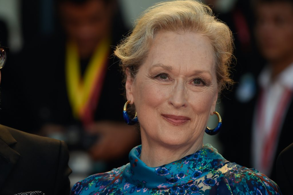 Meryl Streep smiling in front of a blurred crowd