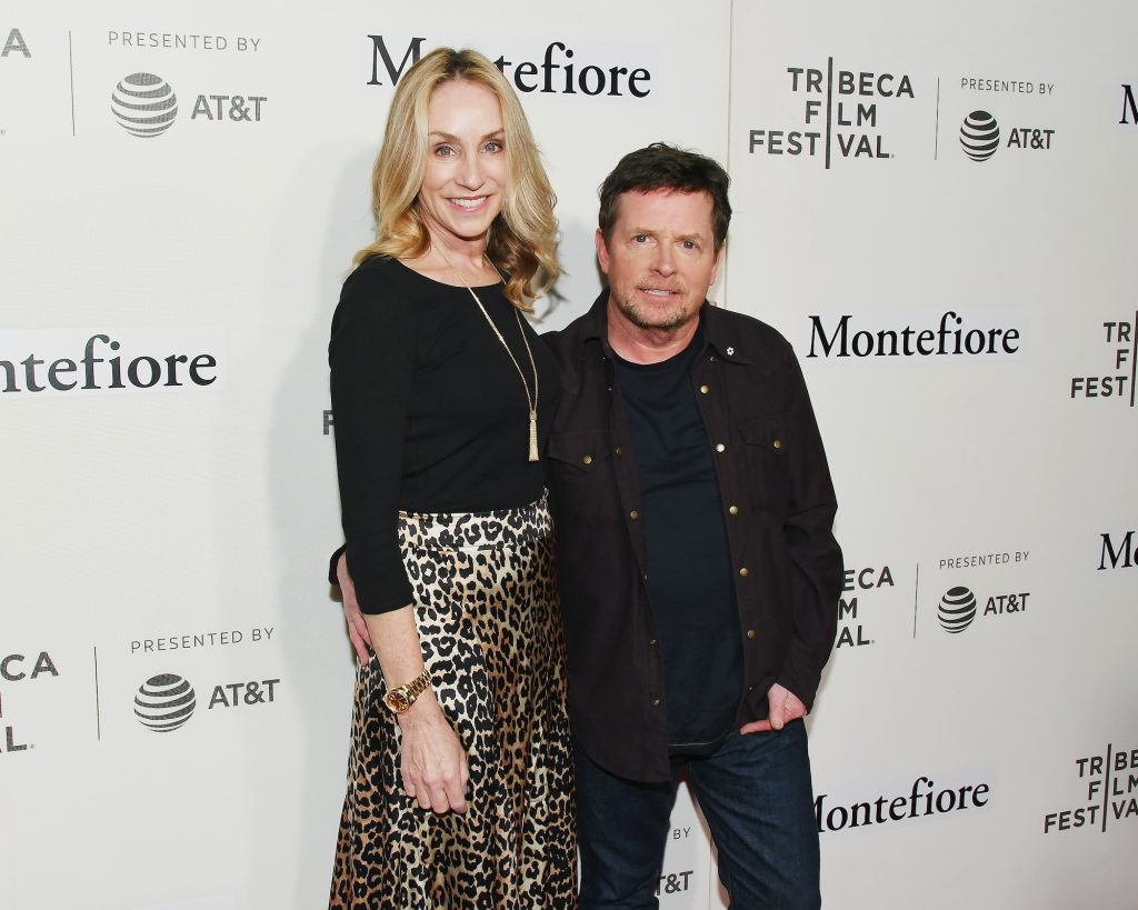 (L-R) Tracy Pollan and Michael J. Fox smiling in front of a white background with repeating logos