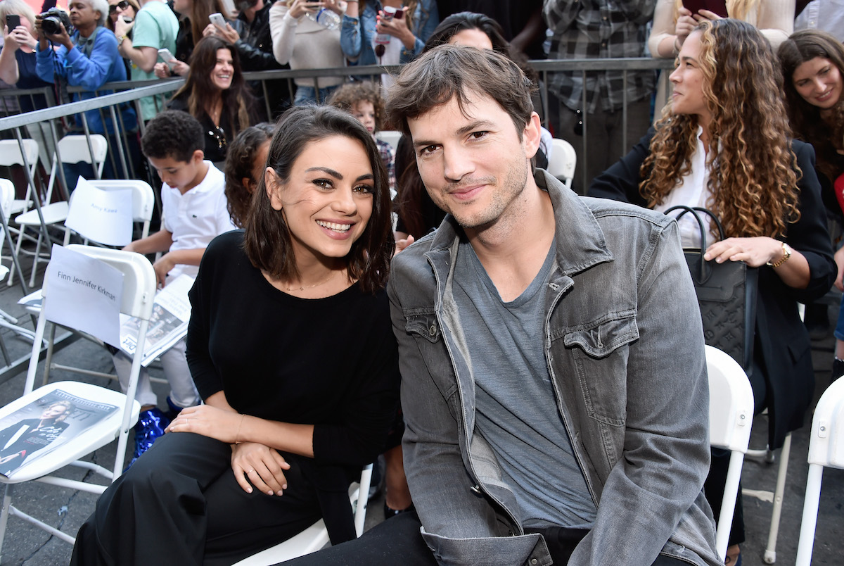 Mila Kunis and Ashton Kutcher smile as they next to each other at the Zoe Saldana Walk of Fame Star Ceremony