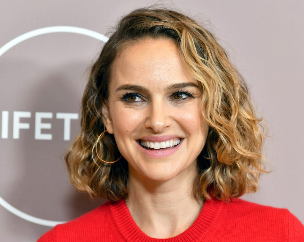 Natalie Portman with curly hair smiling and wearing a red sweater and gold earrings | Amy Sussman/FilmMagic