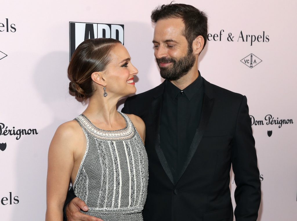 Natalie Portman and Benjamin Millepied look at each other and smile on a red carpet | Jerritt Clark/Getty Images for Dom Pérignon