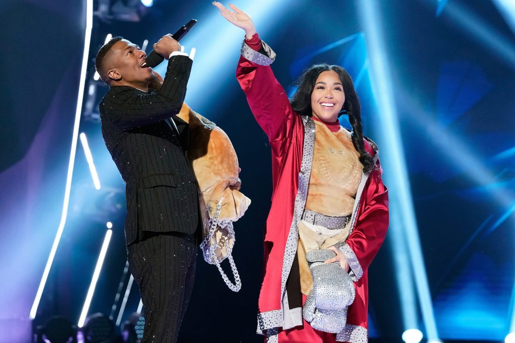 Nick Cannon next to 'Masked Singer' star Jordyn Woods waving to the cameras on 'The Masked Singer'