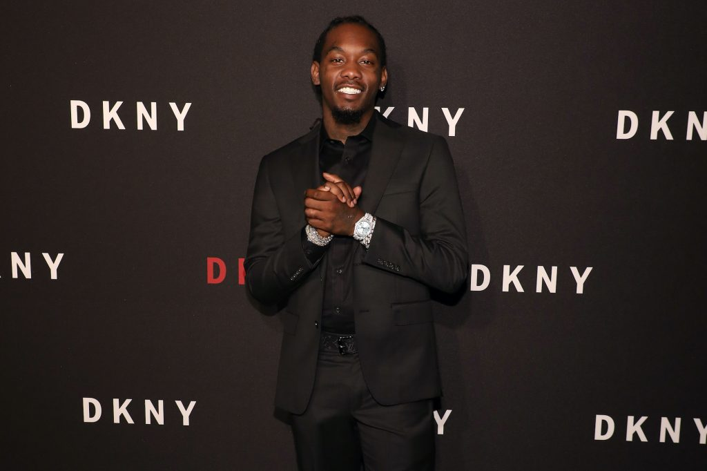 Offset smiling in front of a dark gray background