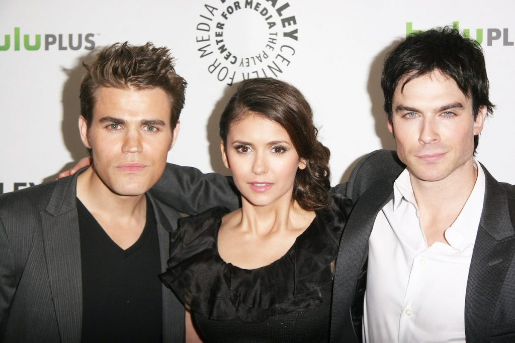 Paul Wesley, Nina Dobrev, and Ian Somerhalder wearing black and white and standing in front of a white and green backdrop   Tommaso Boddi/WireImage