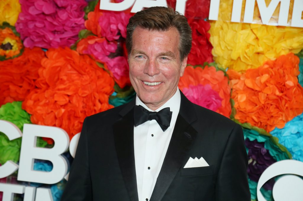 Peter Bergman smiling in front of a multi colored background