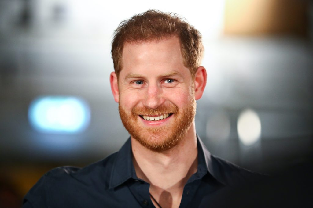 Prince Harry smiling in front of a blurred background