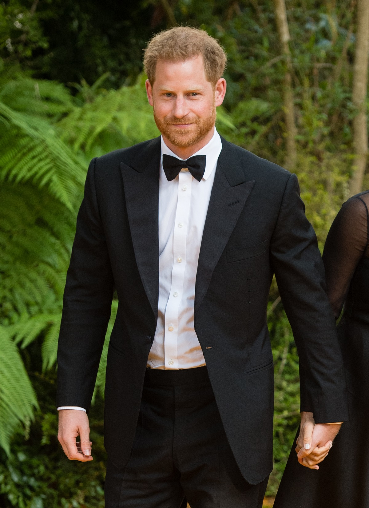Prince Harry, Duke of Sussex, in a suit, holding hands with Meghan Markle (not fully pictured) at 'The Lion King' European Premiere at Leicester Square in London in 2019