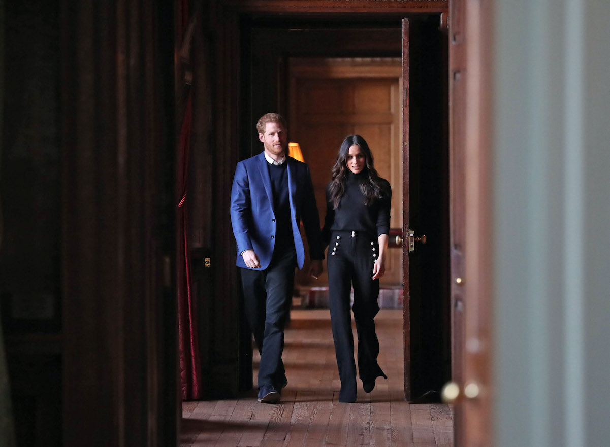 Prince Harry and Meghan Markle hold hands as they walk down a hallway