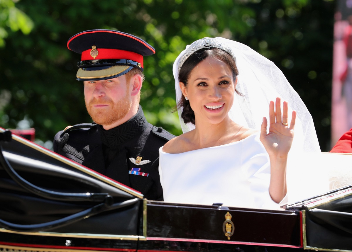 Prince Harry, Duke of Sussex and Meghan, Duchess of Sussex leave Windsor Castle in the Ascot Landau carriage during a procession after getting married at St Georges Chapel on May 19, 2018 in Windsor, England