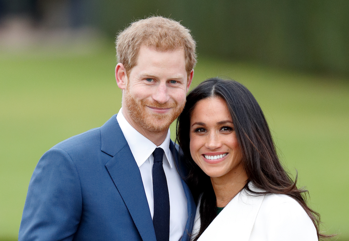 Prince Harry and Meghan Markle smile as they pose for photographers at their engagement photo call