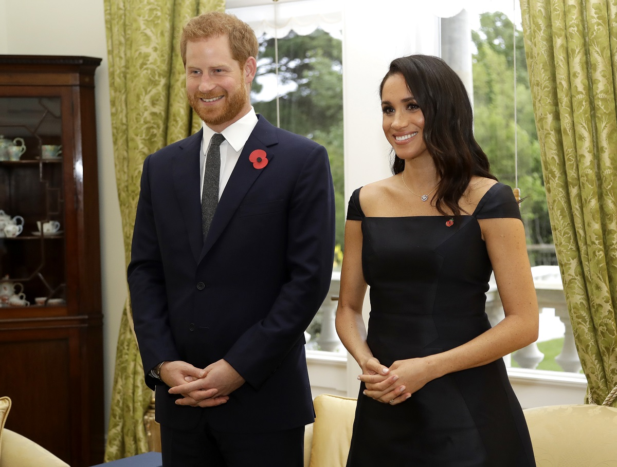 Prince Harry, Duke of Sussex, and Meghan, Duchess of Sussex, in a candid smiling shot as they wait to meet New Zealand Prime Minister Jacinda Ardern, at Government House on October 28, 2018 in Wellington, New Zealand